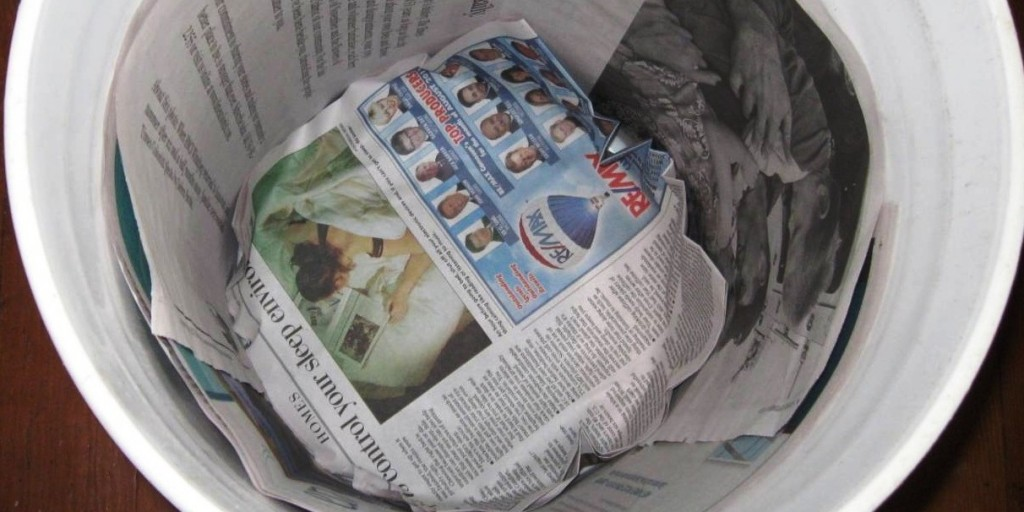 lining a compost pail with newspaper - Kitchen Composting Pail